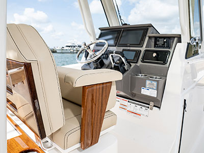 Detail of S 288 Sport boat helm seating with teak accents and command console with steering and controls.