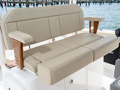 Detail of S 288 Sport boat helm seating with teak accents, split bolster and foldable armrests.