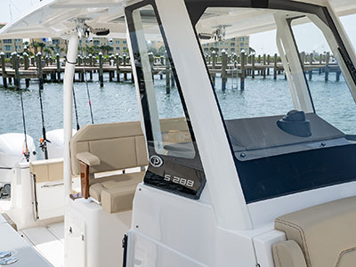 Detail front starboard corner view of S 288 Sport boat windshield, seating, and hardtop.
