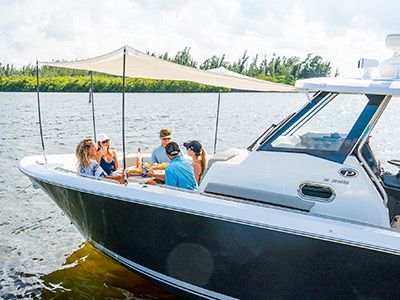 A group of happy boaters dine under the sunshade on the bow of Pursuit Boats S 358 Sport boat.