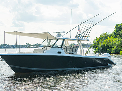 The Pursuit S 358 Sport boat is a center console boat in carbon color and is floating on the water in Ft. Pierce.