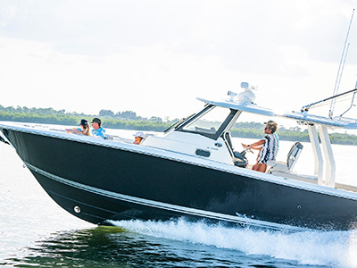 A woman at the helm of Pursuit Boats S 358 Sport Center Console boat running.
