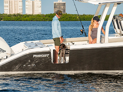 A dog onboard a Pursuit Boats S 358 Sport Center Console boat with hull side door.