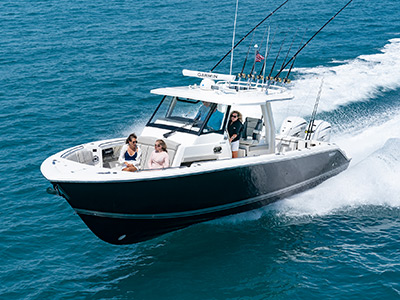 A woman at the helm of Pursuit Boats S 358 Sport Center Console Boat running offshore.