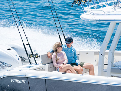 A couple enjoys the boating lifestyle on the Pursuit S 358 Center Console Sport cruising boat.