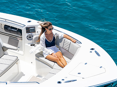 A woman lounges on the bow of Pursuit's new boat – the S 358 Sport Center Console boat on lounge seating.