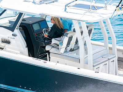 A woman running the all new Pursuit S 358 Sport Boat with oversized hardtop offshore.
