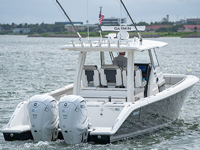 A view of the Pursuit Boat's S 358 Sport Center Console boat with twin Yamaha engines as it cruises away.