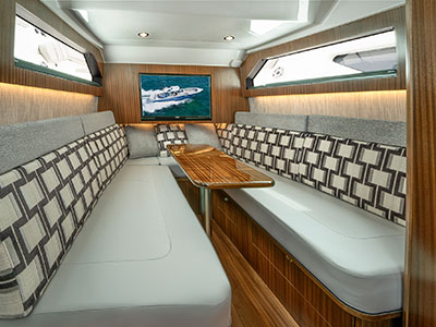 A shot of the luxurious cabin with table on the S 428 Pursuit Sport Center Console Boat.