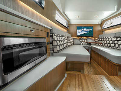 A shot of microwave and gally with V-Berth set up for entertaining in the cabin of the S 428 Pursuit Sport Center Console Boat.