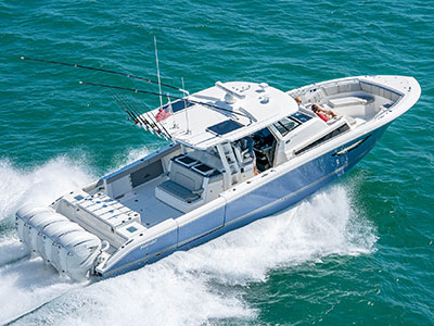 Aerial rear three quarter view of Gulf Stream Blue S 428 Sport center console boat running right with fishing gear.