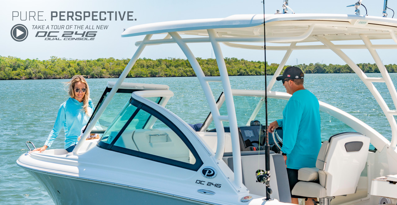 A couple enjoys a day on the water ready to fish or cruise on a 25' DC 246 Pursuit dual console boat. Text over graphic. PURE. PERSPECTIVE. Take a tour of the all new DC 246 Dual Console.
