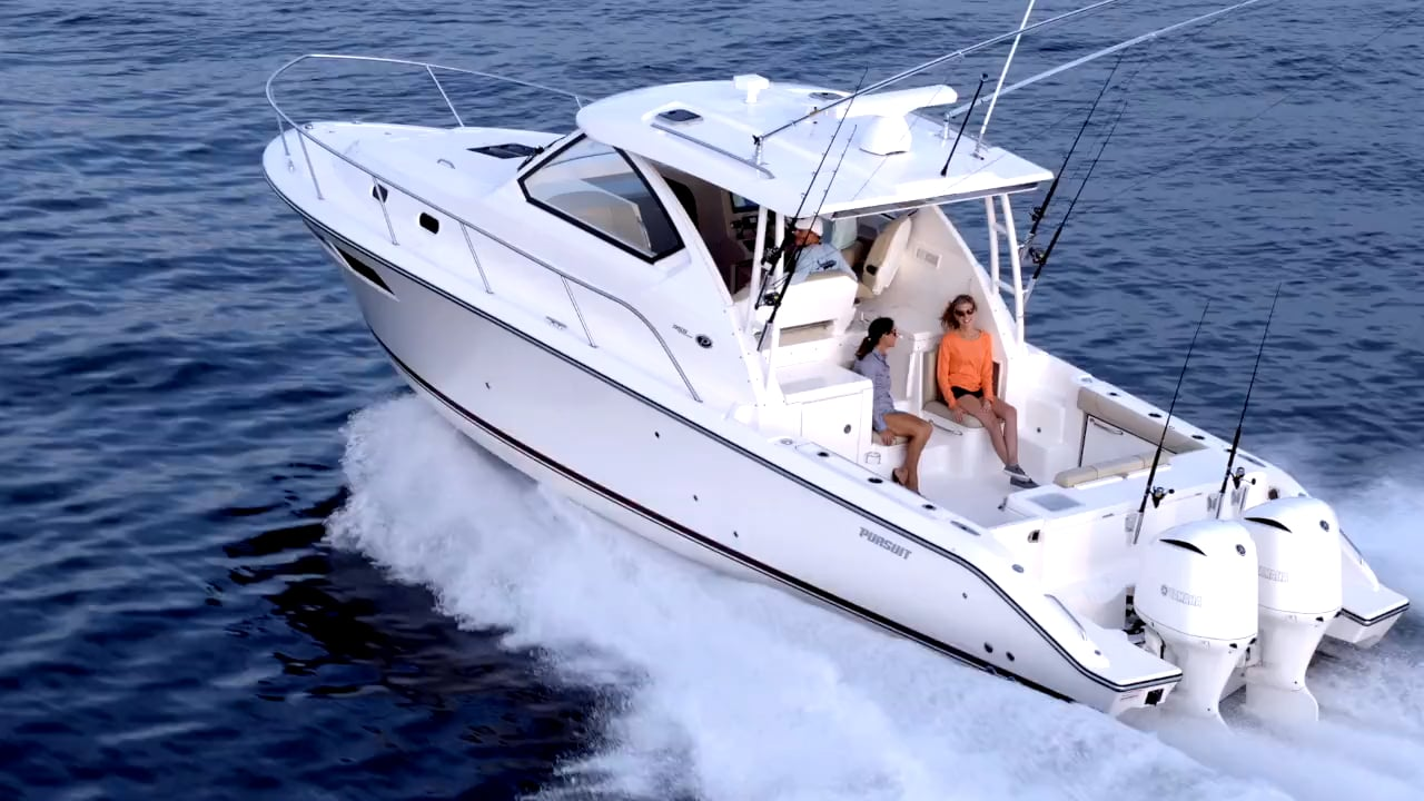Aerial profile view of white OS 355 offshore boat with liveaboard space and twin Yamaha outboard engines running left.