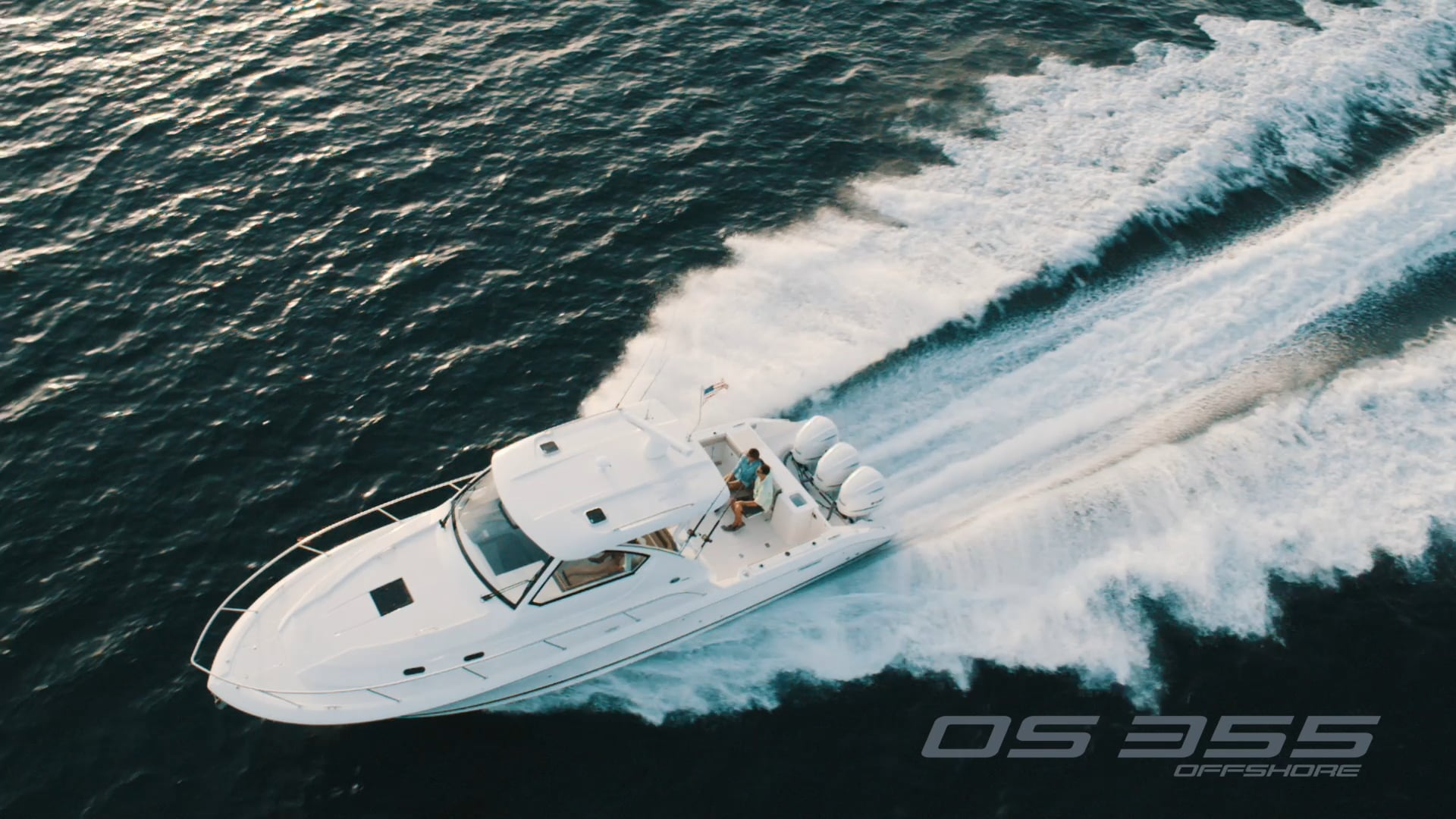Aerial overhead view of white OS 355 offshore boat running left offshore with triple outboard engines.