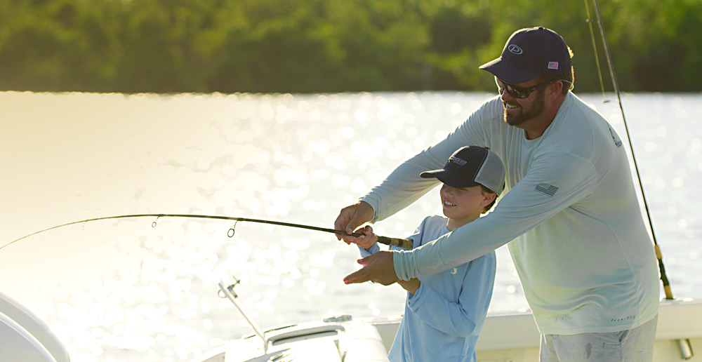 Father and son fishing from the transom of a Pursuit Boat.
