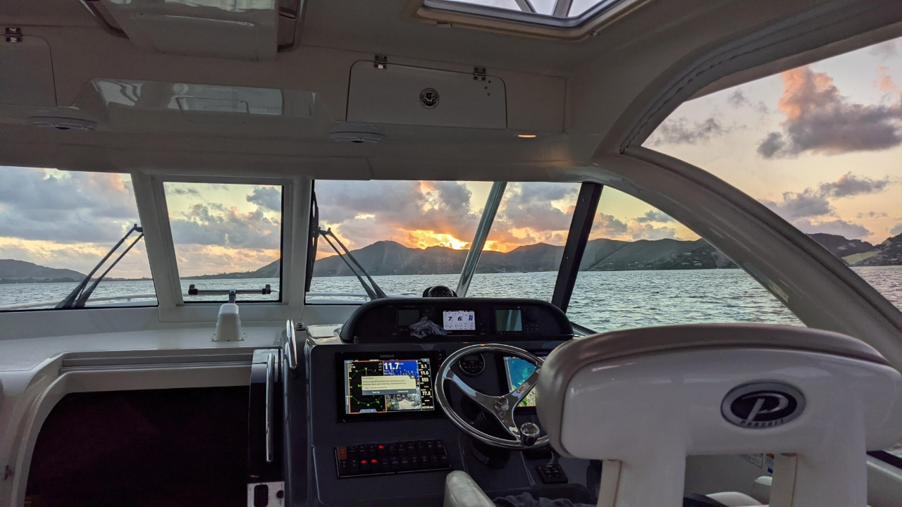 A view of mountains through the tempered windshield on a Pursuit Offshore boat