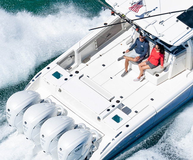 Aerial overhead rear view of Gulf Stream Blue S 428 Sport center console boat running right with quad Yamaha outboard engines and oversized hardtop.