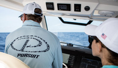 Photo with back of Pursuit shirt with fish in shape of logo shown